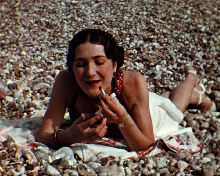 colour photo of female laying on the beach applying lipstick