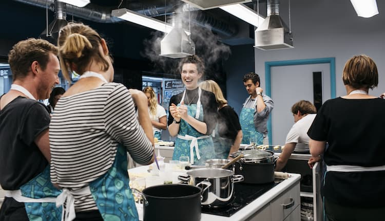 Males and females in an industrial kitchen laughing