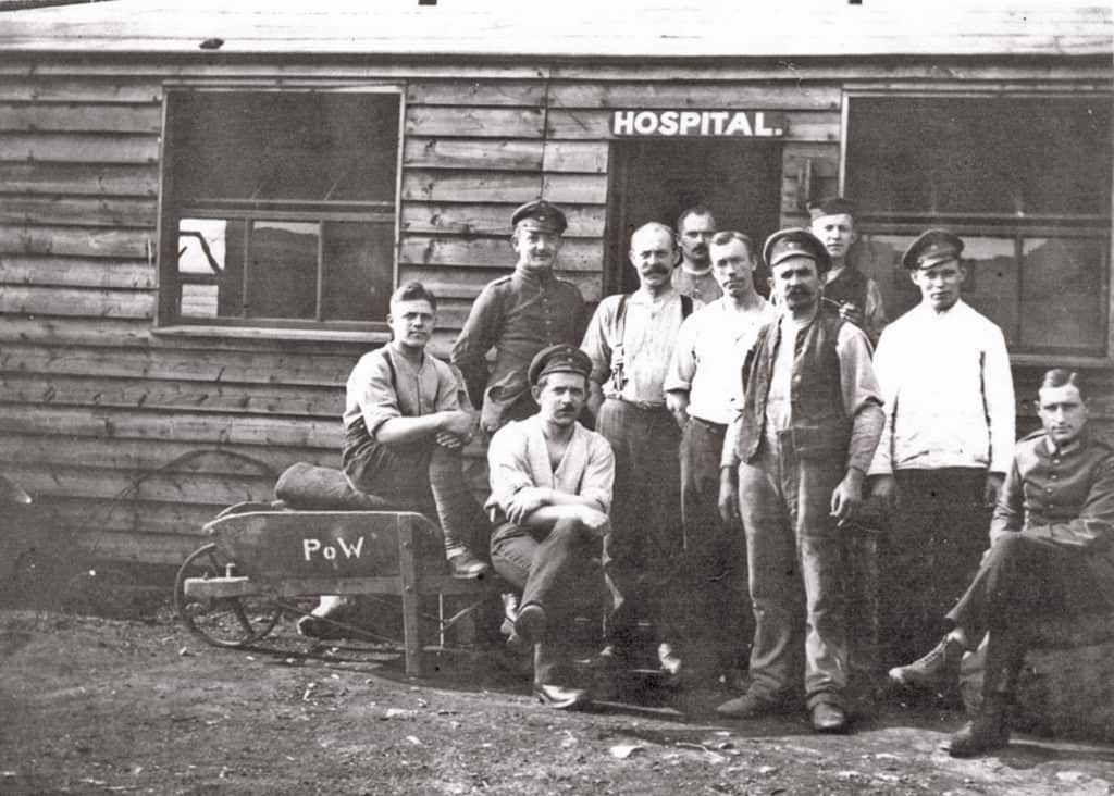 Black and white image of men standing outside the camp hospital