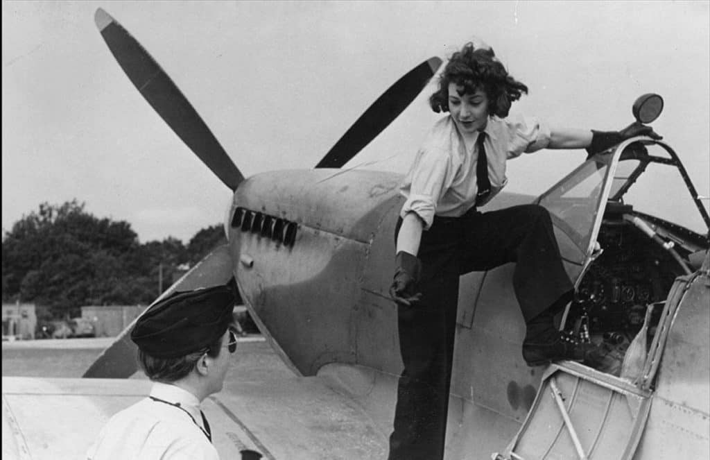 Archive image of a female standing on the wing of an aeroplane reaching down to help another up.