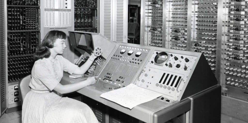 A woman sites in a computer room in the late 1940s/early 1950s
