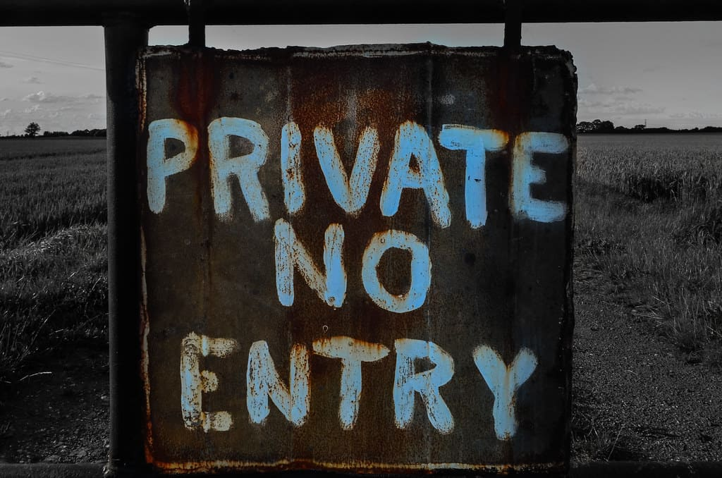 """A wooden sign with the words """"Private no entry"""" painted on"""