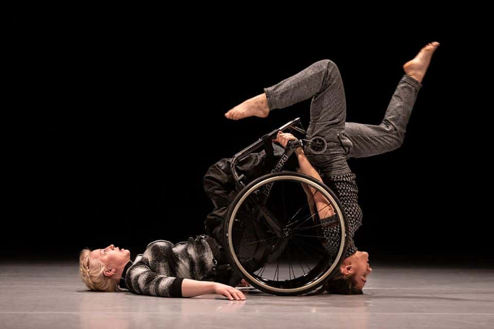 Two white female dancers. The first is a wheelchair user with her back on the ground and legs facing upwards. The other does a headstand against the wheels of her her chair with both her legs off at opposite jaunty angles.